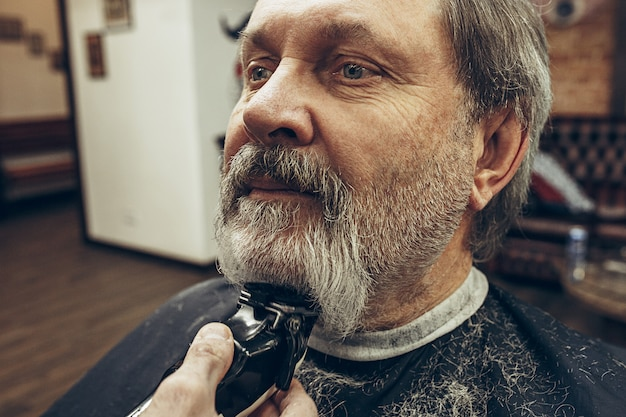 現代の理髪店でグルーミングを身に着けているハンサムなシニアのひげを生やした白人男性のクローズアップ側ビューの肖像画。