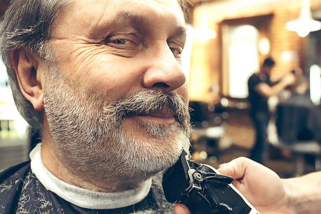 현대 이발소에서 수염 손질을 받고 잘 생긴 수석 수염 된 백인 남자의 확대 측면보기 초상화.