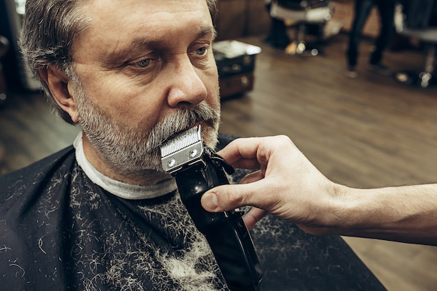モダンな理髪店でひげのグルーミングを取得するハンサムなシニアのひげを生やした白人男性のクローズアップ側ビューの肖像画。