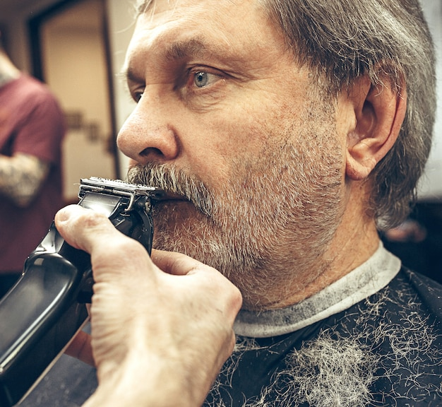 Портрет взгляда со стороны конца-вверх красивого старшего бородатого кавказского человека получая холить бороды в современной парикмахерскае.