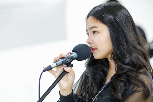 Крупным планом вид сбоку портрет выстрел азиатского подросткового певца, поющего песню с микрофоном. счастливый младший студент-вокалист, практикующий в студии. красивая девушка репетирует, чтобы подготовиться к конкурсу