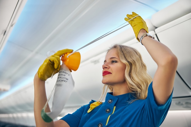 Close up side view portrait of smiling blonde flight attendant in blue uniform showing protective air mask for safety on board