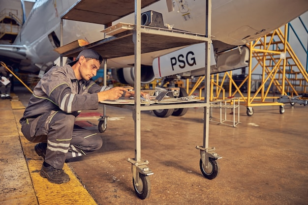 Close up side view portrait of young technical mechanic sitting hunker down while using special equipment in the aviation hangar