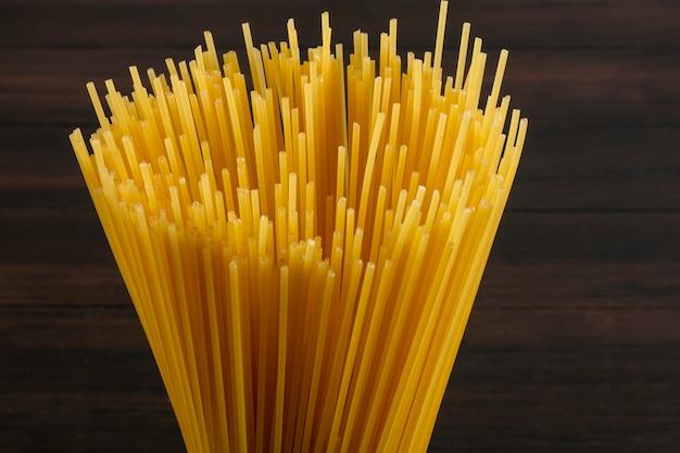 Крупным планом вид сбоку сырые спагетти на деревянной поверхности