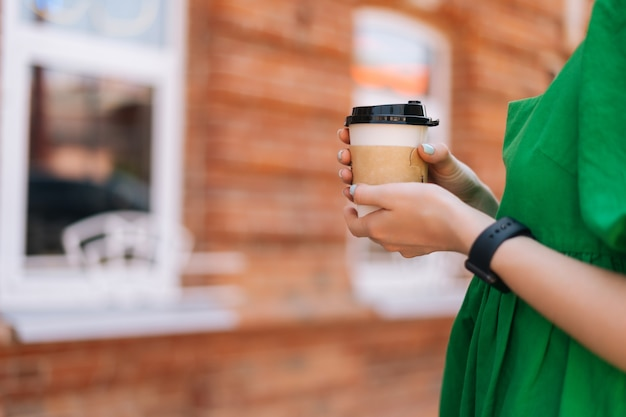 Close-up side view of unrecognizable young woman holding takeaway coffee cup outdoors in city street in summer sunny day on blurred background, selective focus, side view.