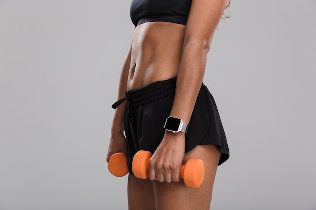 Close up side view of a young african sportswoman holding dumbbells isolated over grey background