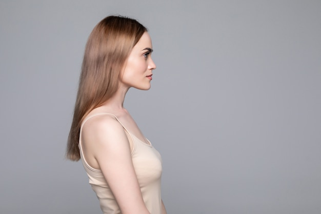 Close up side view of young woman standing isolated grey wall