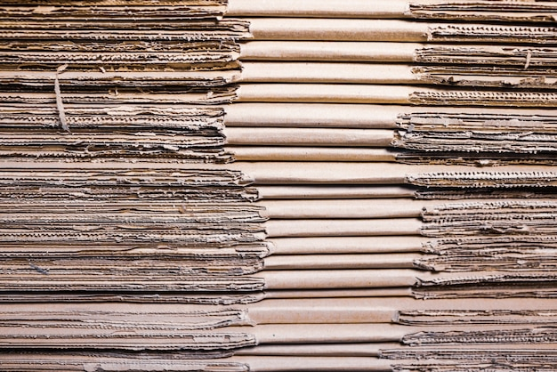 Close-up sides of stacks of cardboard folded on top of each other. concept storage of boxes of environmentally friendly and renewable material.