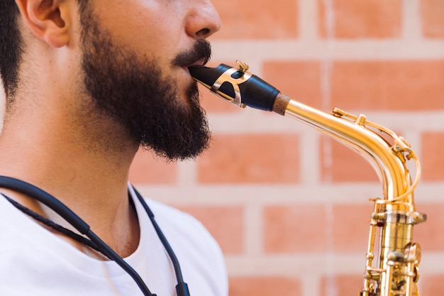 Close up sideways portrait musician playing the saxophone
