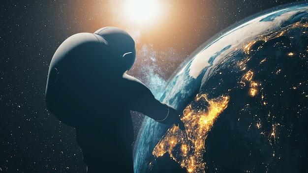 Крупным планом силуэт космонавта: космическая планета земля в солнечном свете в темном звездном небе солнечной системы