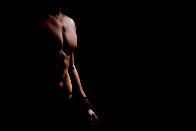 Close-up silhouette of an athletic torso and hands of a man