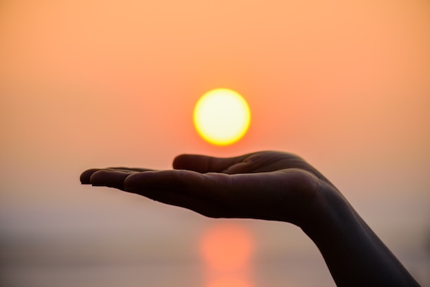 Close up and silhouette of hand holding sun. sun on woman hand.
