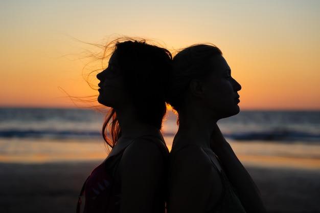 海に沈む夕日のロマンチックなシーンで女性のカップルのシルエットを閉じます。愛の美しい女性の若いレズビアンのカップル。