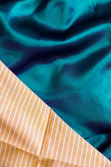 Close-up of silky green textile and orange stripes pattern fabric material