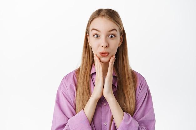 Primo piano di una sciocca ragazza bionda sembra sorpresa e interessata alle notizie, reagisce all'annuncio super cool, tenendosi per mano sul viso, in piedi contro il muro bianco