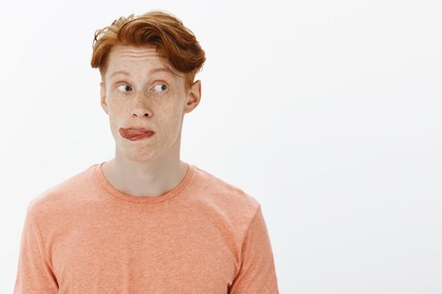 Primo piano di un uomo stupido e carino rossa che sembra proprio curioso e mostra la lingua