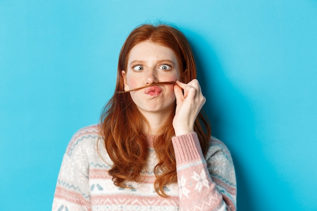Close-up of silly and funny redhead girl making moustache with hair strand and puckered lips, grimacing against blue background