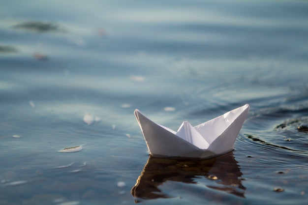 Close-up of simple small white origami paper boat floating quietly in blue clear river or sea water under bright summer sky. freedom, dreams and fantasies concept, copyspace background.