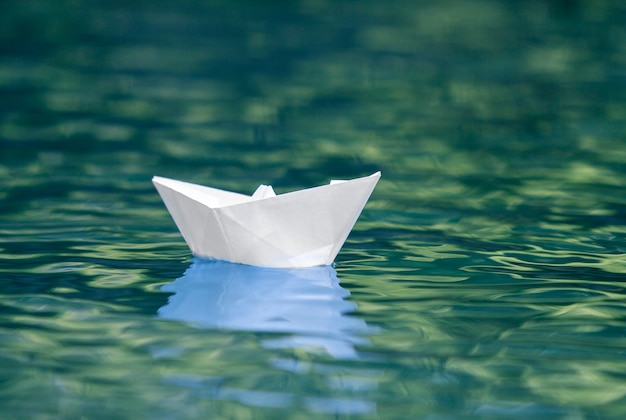 Close-up of simple small white origami paper boat floating quietly in blue clear river or sea water under bright summer sky.