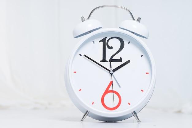 흰색 배경에 고립 된 간단한 흰색 알람 시계를 닫습니다