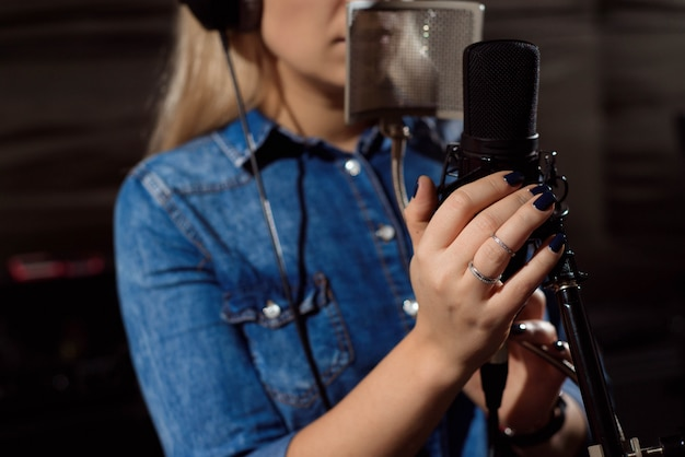 Close up of a singer recording a track in a studio.