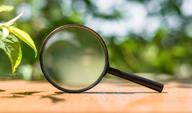 Close up single magnifying glass with black handle, leaning on the wooden table on outdoors.