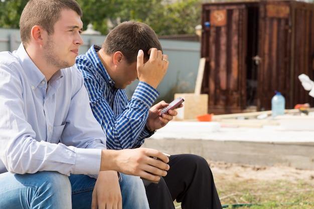 コーナーに座っているサイトエンジニアをクローズアップします。1人は電話で忙しく、もう1人はコーヒーを飲んでいます。