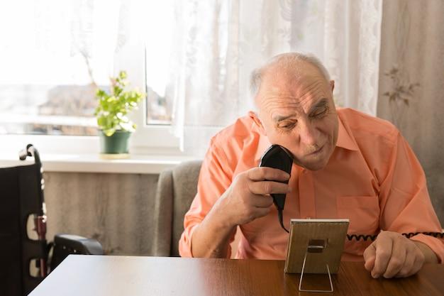 집 안에 있는 나무 탁자에 전기 면도기로 수염을 면도하는 앉아 있는 노인을 닫습니다.