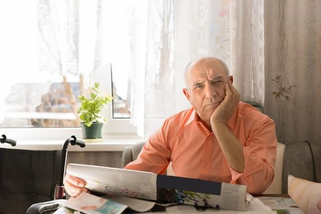 顔に片手でカメラを見ながら新聞を持って座っている老人を閉じます。