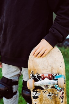 Close up of an skater boy with an old skateboard in front of a graffiti mural