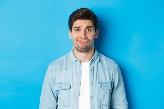 Primo piano di un ragazzo scettico e imbarazzante che sorride, si sente a disagio, in piedi su sfondo blu.