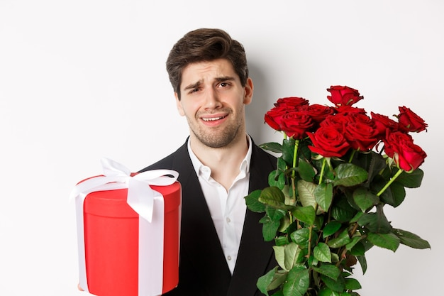 Close-up of skeptical man in suit, holding bouquet of red roses and a gift, standing reluctant against white background.