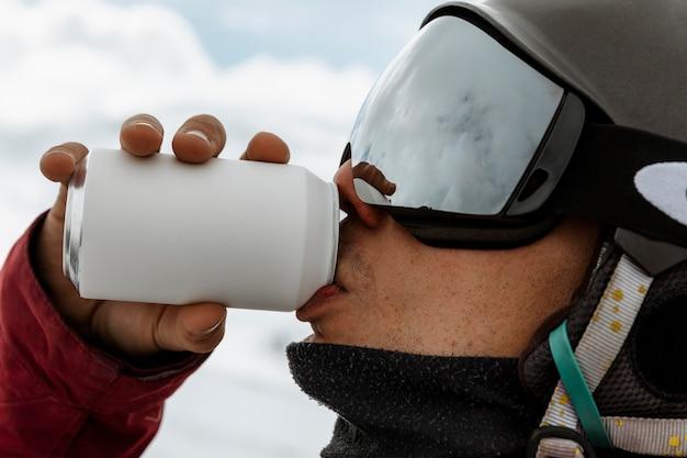 Крупным планом лыжник, пьющий соду