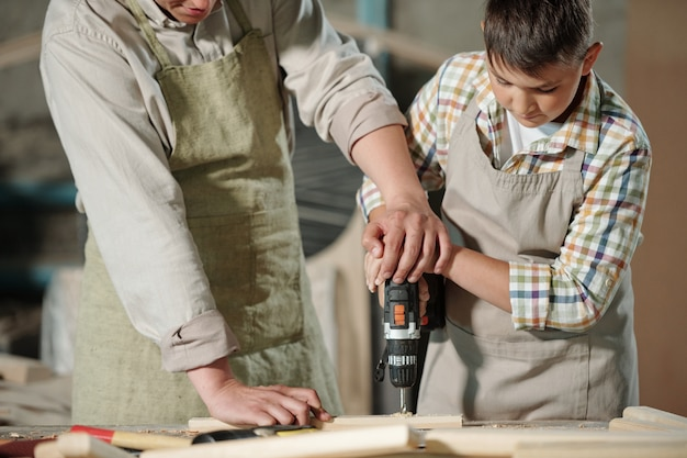 Close-up of skilled carpenter in apron pushing hands of son while helping him to drill wooden surface in workshop