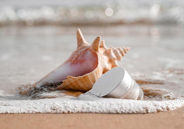 Close-up of skin care moisture recipient arrangement next to seashell