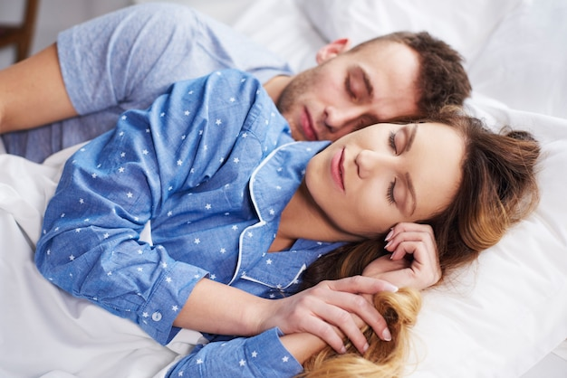 Close up of sleeping together couple in bed