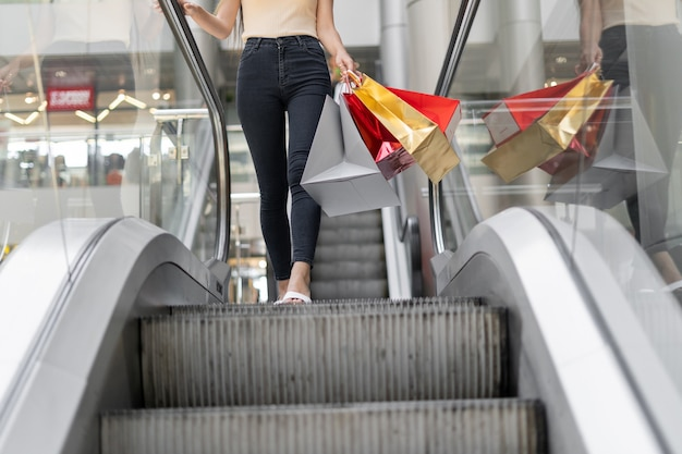 Close-up of slender female legs leaving the escalator in the mall. keep colored bags in your hands. jeans.