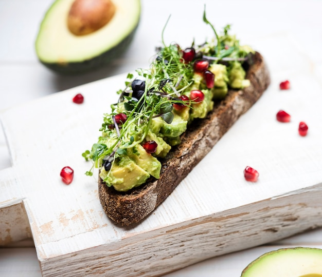 Close-up slice of bread with avocado pasta and pomegranate