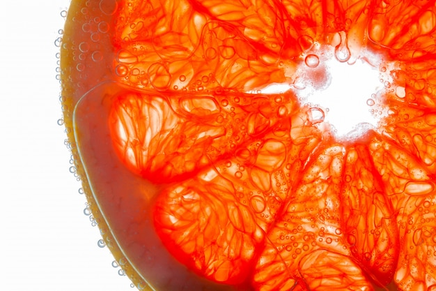 Close-up of slice of grapefruit with ait bubbles on juicy fibers