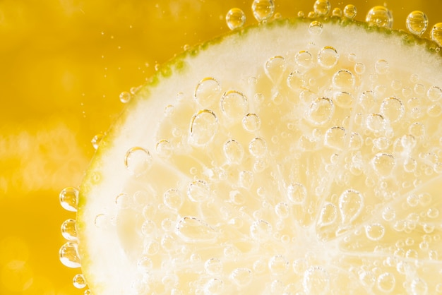 Close-up slice of lemon with water bubbles