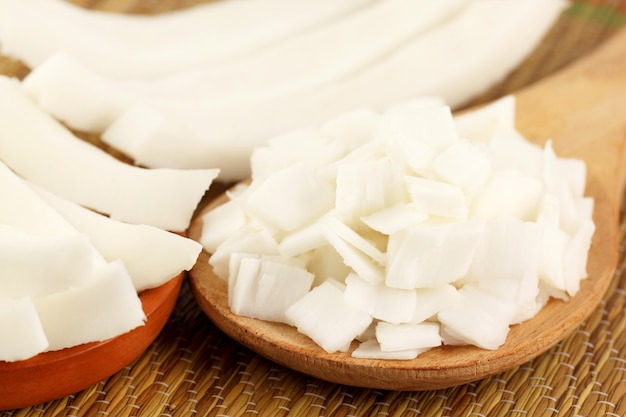 Close up of sliced coconut on wooden spoon