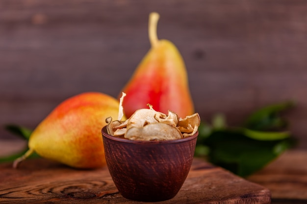 Close-up of sliced homemade dried pear in wooden cup, concept of vegetarian food