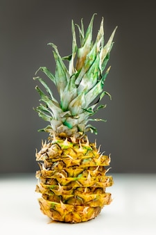 Close-up of sliced pineapple on white and grey background. front view of creatively cut  ripe fresh pineapple