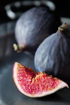 Close-up on a sliced quarter of fresh black fig on a vintage metal plate