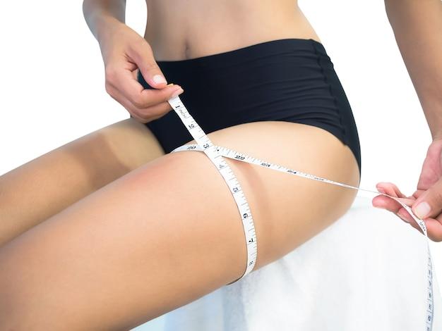 パンティーや減量の記事やダイエットで女性をスリムにするためのビキニでウエスト巻尺のスリムフィットの女性をクローズアップ。格好の良い女の子のコンセプト。