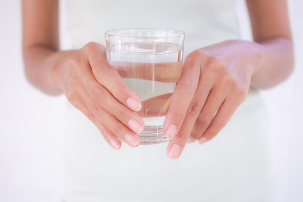 水ガラスを保持しているスリムな手の女性を閉じます。女性の本物のスキンタンと形にフィットします。飲用水で体重を減らし、健康のために。