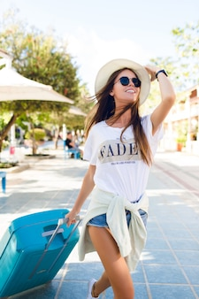 Close-up of slim tanned young girl walking in a park with blue suitcase behind her. she wears denim shorts, white t-shirt, straw hat, and dark sunglasses. she smiles and hold her hat with one hand