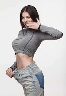 Close-up of slim waist of young woman in big jeans showing successful weight loss
