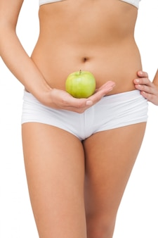 Close up of slim woman holding a green apple