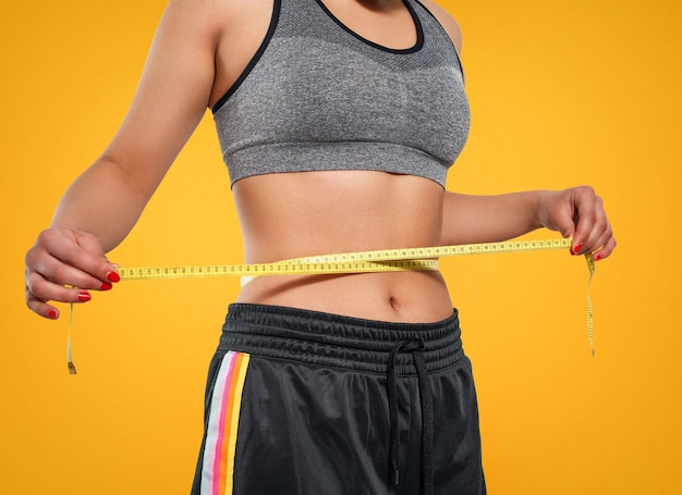 Close up of slim woman measuring her waist's size with tape measure. isolated on yellow background.